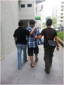 CNB officers escorting a suspected drug offender arrested in the island-wide operation
